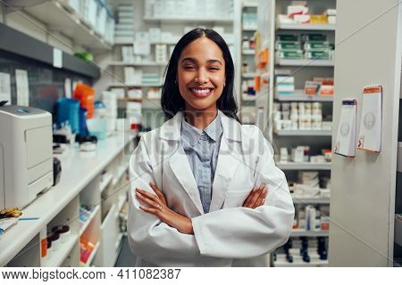 Cheerful Young African American Female Pharmacist Wearing Labcoat With Folded Hands Standing In Chem