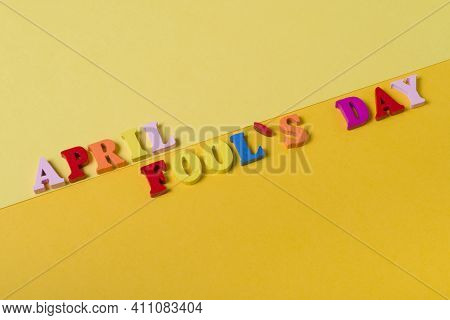 Wooden Letters The First Of April On A Yellow Background. The Concept Of The Holiday,