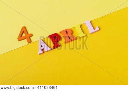 Wooden Letters Of The Fourth Of April On A Yellow Background.