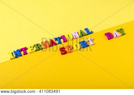Wooden Letters International Sports Day On A Yellow Background.