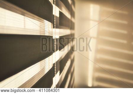 Sun Shining Through Window Blinds Throwing Shadows On The Wall