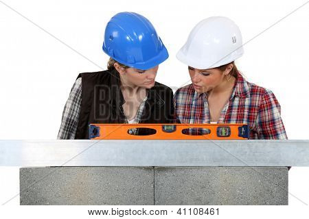 Tradeswomen examining a blueprint together