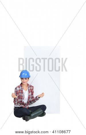 A female construction worker in the lotus position.