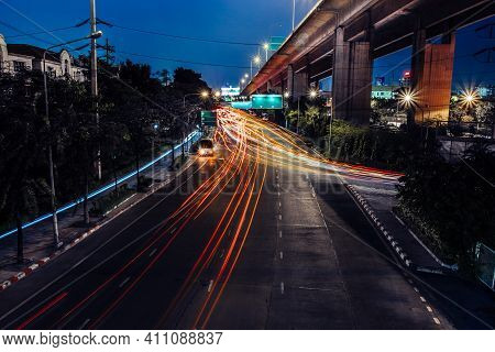 Car Lights At Night On The Road Going To The City. Aerial View Of The Speed Traffic Trails On Motorw