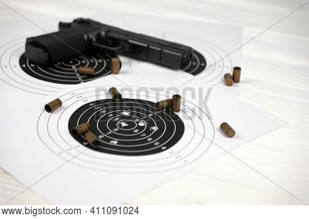 Gun And Many Bullets Shooting Targets On White Table In Shooting Range Polygon. Training For Aiming