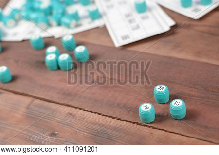 Many Barrels With Numbers And Cards For Lotto Or Russian Bingo Table Game On Wooden Surface. Russian