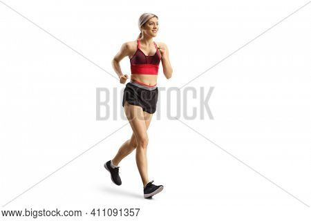 Full length shot of a blond young female in sportswear running isolated on white background