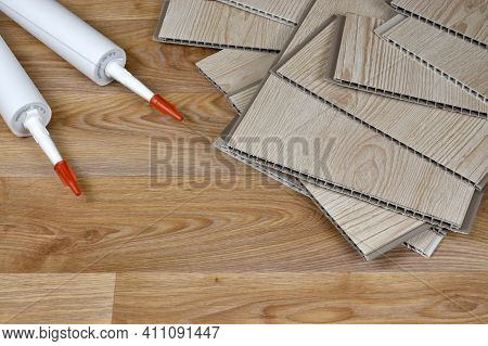 Set Of Items For Pvc Ceiling Indoor Works. Assembly Adhesive Bottles And Pvc Panels. Indoor Vpc Sidi