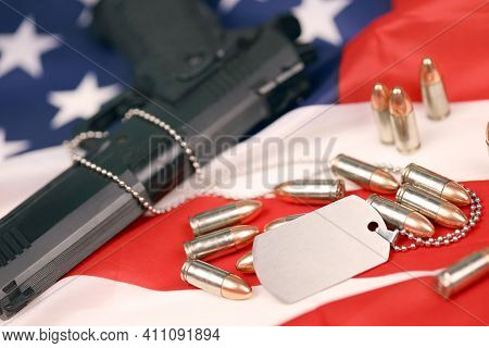 Many Yellow 9mm Bullets And Gun With Dogtags On United States Flag. Concept Of Duty And Service In U