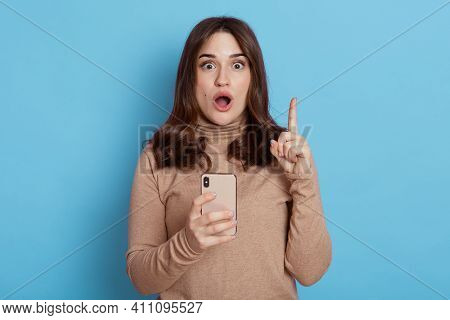 Astonished Young Woman Girl In Beige Turtleneck Posing Isolated On Blue Background, Holding Mobile P