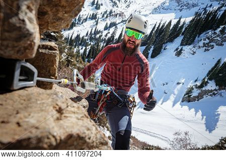 Frightened Bearded Climber Hangs On The Belay. High-altitude Mountaineering In Winter. A Man Climbs