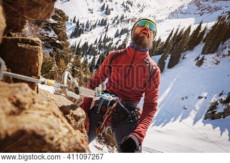 Bearded Climber, Secured With A Belay Device, Looks At The Top Of The Cliff. Winter Alpine Mountaine