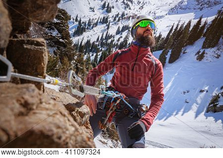 A Bearded Climber, Strapped In With A Safety Device, Takes A Breath While Admiring The Landscape. Wi