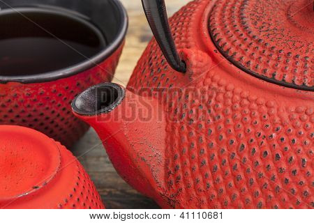 red tetsubin with a cup of tea - a detail of a traditional cast iron Japanese teapot