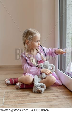 A little girl looks at a pigeon outside the window