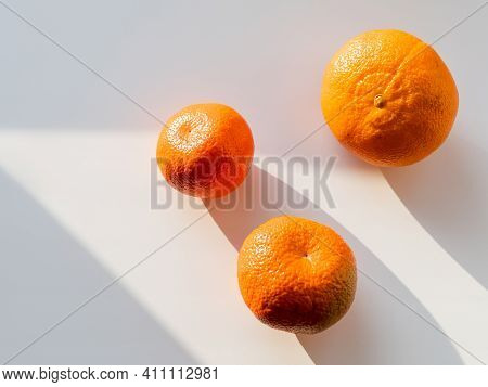 Three Tangerines On White Background. Ripe Fruits On Sunlight. Top View On Bright Orange Citruses Wi