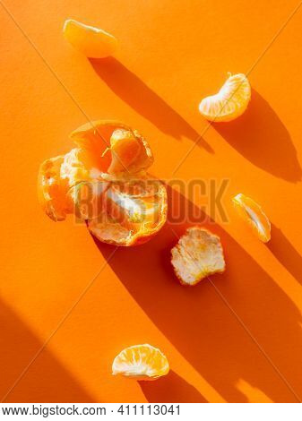 Top View Of A Peeled Tangerine. Peel And Pieces Of Citrus On Bright Orange Background. Ripe Fruit On