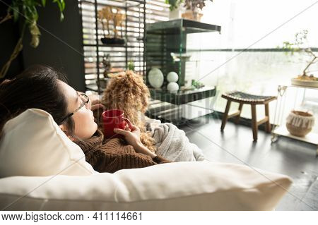 Young Woman Happily Lying On The Sofa At Home, Holding A Red Cup Of Coffee While Petting Her Adorabl