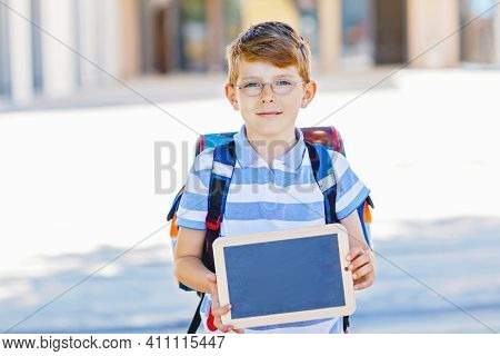 Happy Little Kid Boy With Backpack Or Satchel And Glasses. Schoolkid On The Way To School. Healthy A