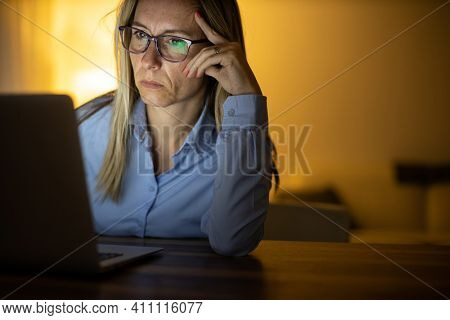 Pretty, middle-aged woman working late in the day on a laptop computer at home, running a business from home, working remotely - getting frustrated
