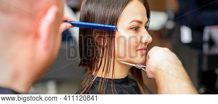 Male Hairdresser Cuts Wet Hair Of Young Caucasian Woman Combing With A Comb In A Hair Salon