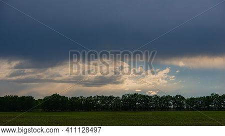 Rain Clouds Strip Of Deciduous Forest And Green Field, Panoramic Landscape. Spring Season, May. Web