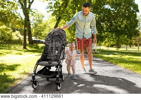 family, fatherhood and people concept - happy father with child in stroller walking at summer park