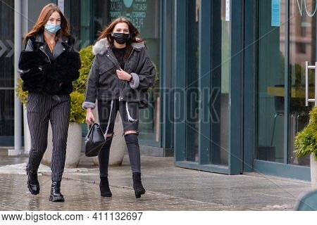 Vilnius, Lithuania - March 5 2021: Beautiful Couple Of Young Girls Wearing Masks And Walking In The