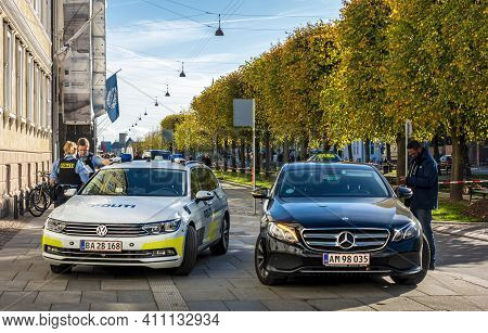 Copenhagen, Denmark - Oct 19, 2018: Police Officers Standing Beside Their Vehicle. Pedestrians Aroun