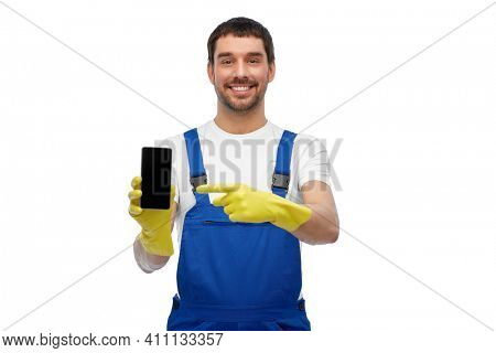 profession, cleaning service and people concept - happy smiling male worker or cleaner in overall and gloves showing smartphone over white background