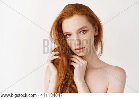 Beauty. Young Woman With Natural Shiny Red Hair And Perfect Pale Skin Looking At Camera, Sensual Gaz