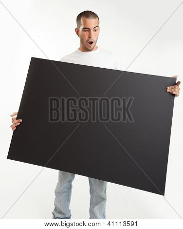 Young man holding a blackboard, with a surprised expression
