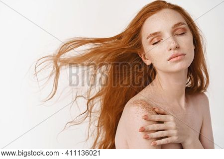 Close-up Of Tender Young Woman With Long Natural Red Hair Flying In Air, Close Eyes And Relaxing On