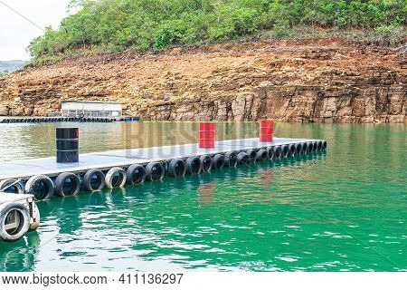 Floating Platform Made Of Barrels And Tires In The Middle Of The Lake. Floating Walkway. Photo Taken