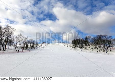 Ski Slope With Few Ski Riders Skiing In The Morning At Ski Resort With Beautiful Winter Weather Fron