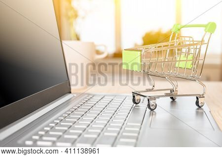 Online Shopping And Delivery Concept. Small Shopping Trolley Standing On Laptop Keyboard. Shopping C