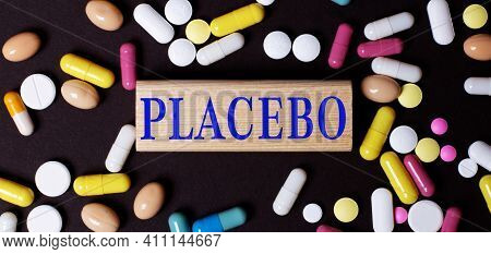 On A Dark Background, Multi-colored Pills And The Word Placebo On A Wooden Block. Medical Concept