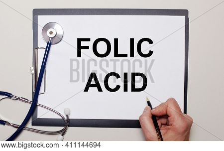 On A Light Background, A Stethoscope And A Sheet Of Paper, On Which A Man Writes Folic Acid. Medical