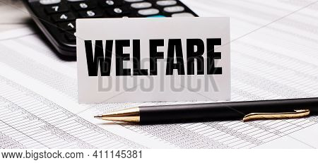 On The Table There Are Reports, A Pen, A Calculator And A White Card With The Text Welfare. Defocus