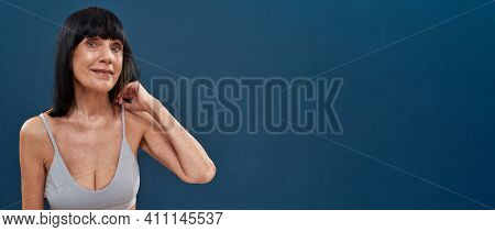 Beautiful Middle Aged Caucasian Woman With Age Wrinkles Around Eyes Posing On Dark Blue Background,
