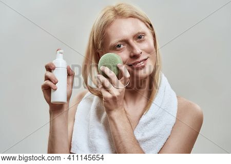 Smiling Young Caucasian Man With Long Fair Hair Using Facial Sponge And Cleaning Foam While Posing O