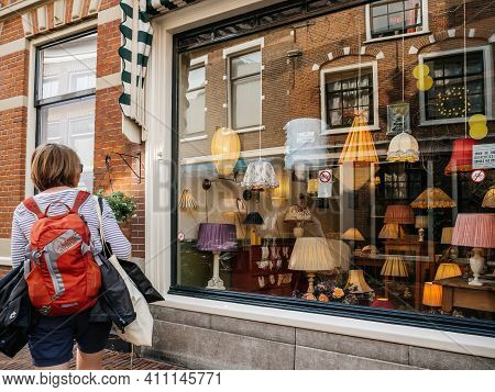 Haarlem, Netherlands - Aug 21, 2018: Rear View Of Dutch Woman With Red Backpack Sightseeing The Beau