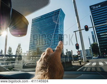 The Hague, Netherlands - Aug 21, 2018: Pov Male Hand Pointing From The Car Window To The Tall Skyscr