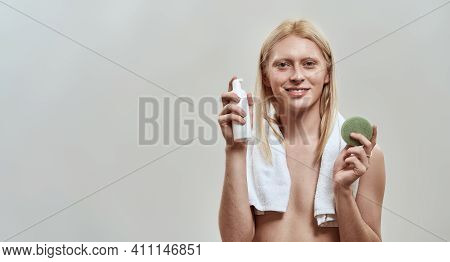 Happy Young Caucasian Man With Long Blond Hair Holding Facial Sponge And Cleaning Foam While Posing
