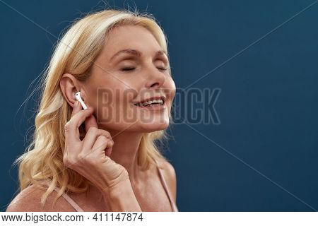 Enjoying Music. Happy Mature Caucasian Woman With Closed Eyes Adjusting Wireless Earphones While Pos