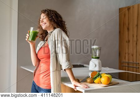 Happy young woman standing in kitchen and holding glass of detox juice. Cheerful girl drinking healthy smoothie at home. Beautiful smiling woman drinking green vegetable smoothie.