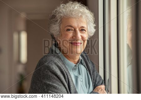Portrait of happy senior woman standing at home near window and looking at camera. Smiling beautiful old woman relaxing at home during Covid quarantine. Cheerful retired old lady relaxing at home.
