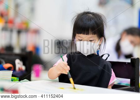 Preschool Girl Wearing Medical White 3d Mask. Children Make Art On Canvases. Cute Kids Wear Apron Wh