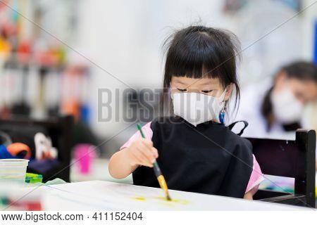 Preschool Girl Wearing Medical White 3d Mask. Children Make Art On Canvases. Cute Kids Wear Apron Wh