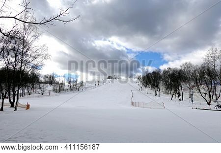 Empty ski slope front view on overcast winter day at ski resort in low season